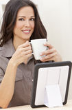 Woman Using Tablet Computer Drinking Tea or Coffee. Beautiful, smiling, young brunette woman at home at a table using her tablet computer drinking a mug of tea royalty free stock images