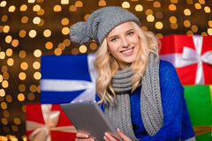 Woman using tablet computer with gift boxes on background Royalty Free Stock Image