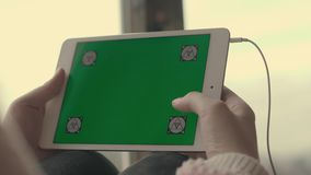 Woman hands using at tablet with green screen and scrolling pages. Woman using at tablet computer with green screen in home. Female scrolling pages. Close up stock footage