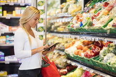 Woman Using Tablet Computer In Grocery Store Royalty Free Stock Images