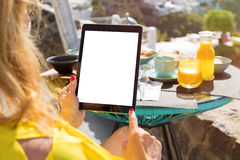 Woman using tablet computer while having breakfast Royalty Free Stock Photos