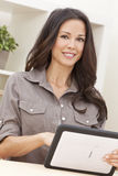 Woman Using Tablet Computer At Home. Beautiful, smiling, young brunette woman at home at a table using her tablet computer stock photos