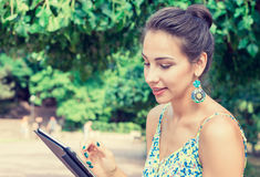 Woman using tablet computer outdoor in park, smiling Royalty Free Stock Photos