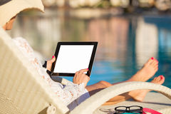 Woman using tablet computer by the pool Stock Photo