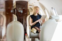 Woman Using Tablet Computer In Private Jet. Rich mid adult woman using tablet computer in private jet stock photo