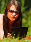 Woman using tablet computer reading outdoors. Royalty Free Stock Image