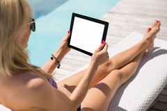 Woman using tablet computer while sitting in deck chair by the pool Royalty Free Stock Photos
