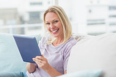 Woman using tablet computer on sofa at home Royalty Free Stock Image