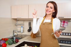 Woman using a tablet computer to cook Stock Image