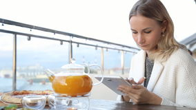 Woman using tablet computer touchscreen in cafe. stock footage