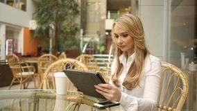Woman using tablet computer touchscreen in cafe stock footage