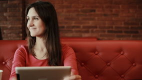 Woman using tablet computer touchscreen, drinking coffee in cafe. Woman using tablet computer ipad touchscreen in cafe stock video footage