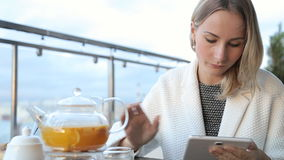 Woman using tablet computer touchscreen, drinking tea in cafe stock video footage