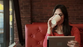 Woman using tablet computer touchscreen, drinking tea in cafe. Woman using tablet computer ipad touchscreen, drinking tea in cafe stock footage