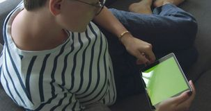 Woman using tablet computer touchscreen. In green closeup stock video footage