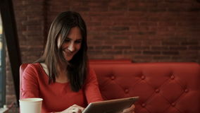 Woman using tablet computer touchscreen and laughs in cafe