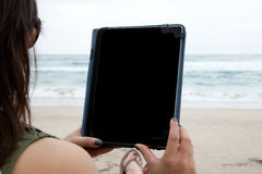 Woman using tablet device while on a beach Royalty Free Stock Images