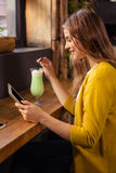 Woman using tablet and drinking milkshake Stock Photography