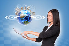 Woman using tablet. Earth with buildings and wire- Royalty Free Stock Images