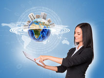 Woman using tablet. Earth with buildings and world Royalty Free Stock Photography
