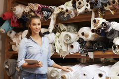 Woman using tablet in fabric storage warehouse, portrait Stock Photography