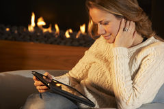 Woman using tablet in front of fire at home Stock Images