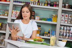 Woman Using Tablet While Having Snacks In Royalty Free Stock Photos