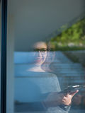 Woman using tablet at home by the window Stock Image