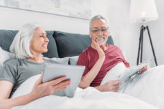 Woman using tablet while husband reading newspaper in bed Stock Photos