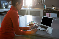 Woman using tablet at kitchen counter. Young woman using digital tablet at counter in kitchen Royalty Free Stock Images