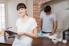 Woman using tablet in kitchen. While men ironing a shirt in background Stock Photo