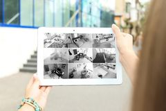 Woman using tablet for monitoring CCTV cameras. Outdoors. Home security system royalty free stock photos