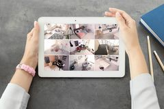 Woman using tablet for monitoring CCTV cameras. At table. Home security system stock photo