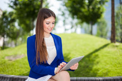 Woman using a tablet outdoor. Portrait of a young woman using a digital tablet Stock Images