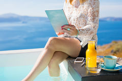 Woman using tablet by outdoor bathtub Royalty Free Stock Image