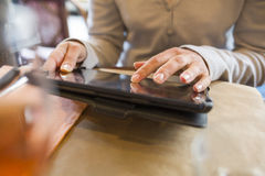 Woman using tablet pc in a cafe, vacation pictures Royalty Free Stock Photo