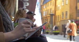 Woman using tablet PC in city street. Close-up shot of a woman working with touch pad with coffee cup in hands. She browsing the Internet on pad in the city stock footage