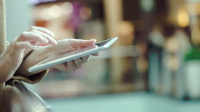 Woman using tablet PC in public place. Close-up shot of female hands typing on touchpad in public place. Defocused interior with people walking in background stock footage