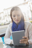 Woman using tablet PC at sidewalk cafe Stock Image