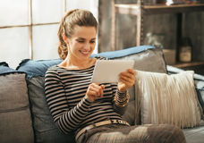 Woman using tablet pc while sitting in apartment Royalty Free Stock Photography