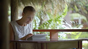 Woman using tablet PC sitting outdoor in tropics. Young woman using tablet computer sitting on outdoor terrace in tropics stock footage