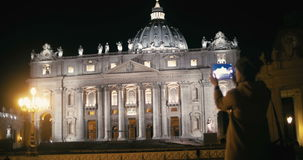 Woman using tablet PC to capture St. Peters. Steadicam shot of a female tourist with pad near St. Peters Basilica in Vatican City at night. She making video or stock video footage