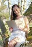 Woman using tablet pc on a tree Stock Photography
