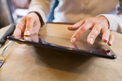 Woman using tablet pcin a cafe, surfing web Stock Photos