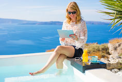 Woman using tablet by the pool Royalty Free Stock Photography