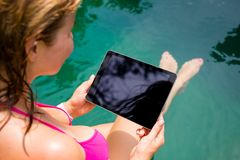 Woman looking at tablet by the pool Stock Image