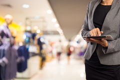 Woman using tablet in shopping mall. Stock Image
