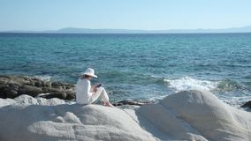 Woman using tablet. Woman sitting on the rock near the sea and using tablet stock footage