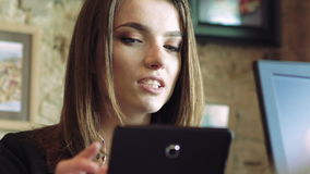 Woman using a tablet, speaking in cafe. Look through coffee evaporate. In FUll HD stock footage
