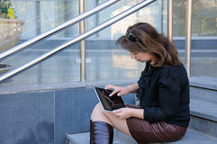 Woman using a tablet on stairs of office building Stock Image